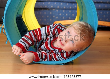 Happy toddler plays indoor in a tunnel