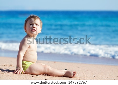Happy toddler sits on sand beach