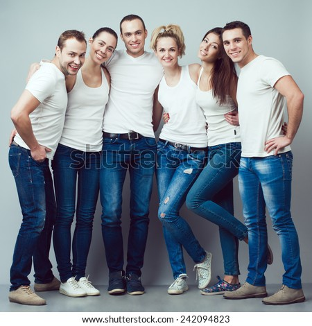 Happy together concept. Group portrait of healthy boys and girls in white t-shirts, sleeveless shirts and blue jeans standing and posing over gray background. Urban style. Studio shot