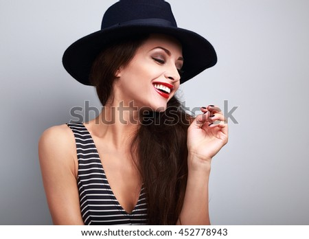 Happy toothy laughing female model profile in black elegant hat on blue background