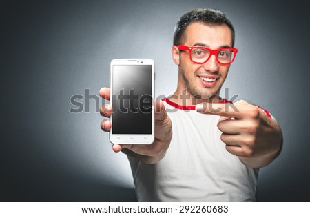 Happy trendy young man showing blank screen of his mobile phone - smartphone space for your text