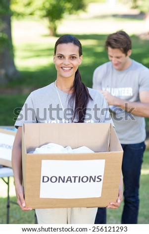 Happy volunteer brunette holding donation box on a sunny day
