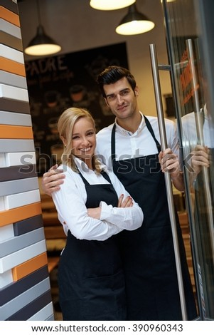 Happy waiter and waitress standing at entrance of cafeteria, smiling, looking at camera.