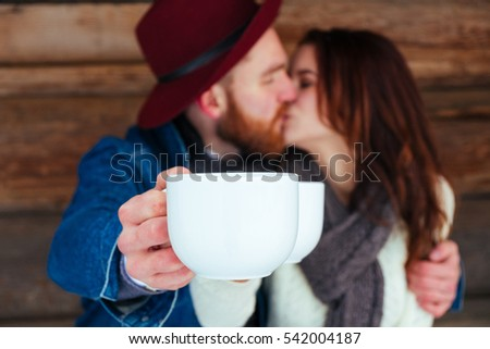 Happy Winter Couple Having Fun Outdoors. Snow.  Vacation. Hot Drink Outdoor. Joyful family