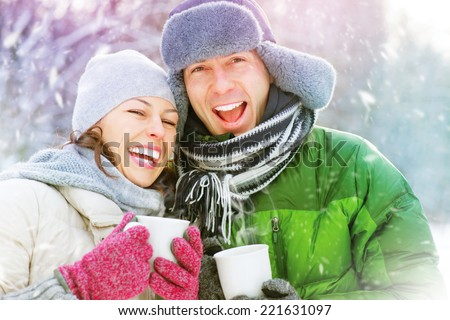 Happy Winter Couple Having Fun Outdoors. Snow. Winter Vacation. Hot Drink Outdoor. Joyful family