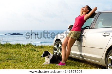 Happy woman and dog enjoying travel and peace on summer. Beautiful girl and her pet on road trip to coast. Copy space.