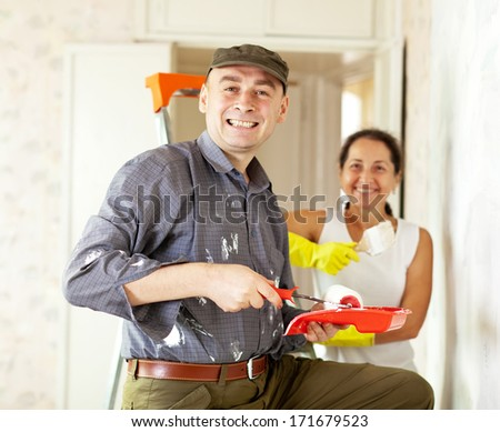 Happy woman and man making repairs at living room