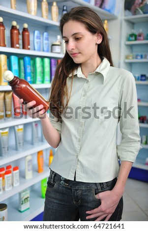 happy woman at pharmacy buying shampoo and reading label