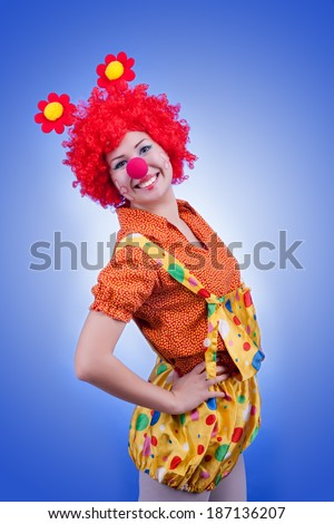 Happy woman clown on blue background. Studio lighting