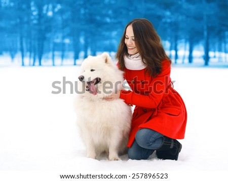 Happy woman having fun with white Samoyed dog outdoors in winter day