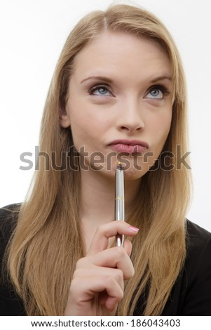 happy woman holding a pen deep in thought