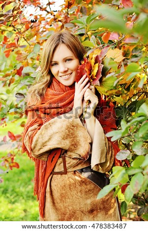 Happy Woman Holding Autumn Leaves in her Hands
