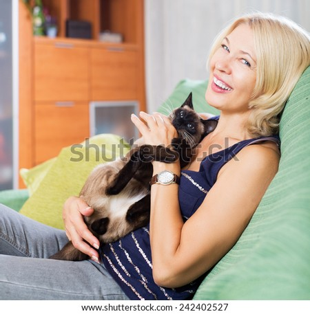 Happy woman holding Siamese kitten in arms and smiling