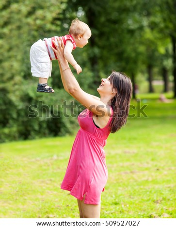 Happy woman holding toddler above head in park