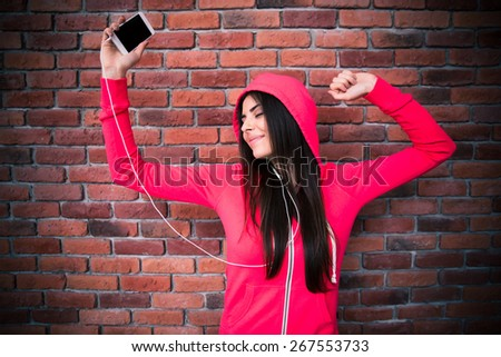Happy woman listening music and dancing in headphones over brick wall