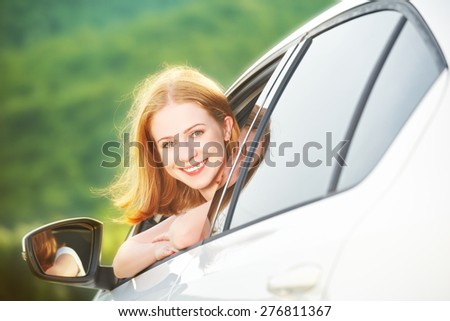 happy woman looks out the car window on nature summer
