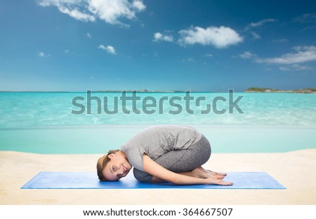happy woman making yoga in child pose on beach