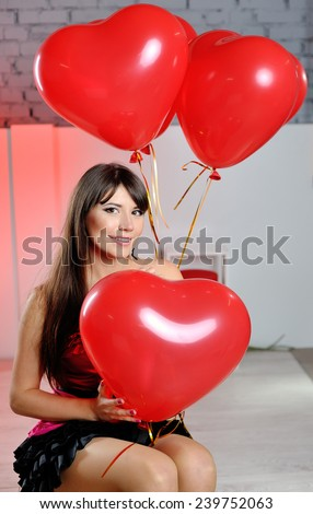 happy woman on Valentine's Day with red balloons in the shape of heart.