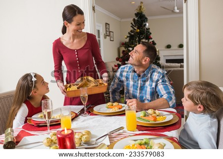 Happy woman serving roast turkey to her family at home in the living room