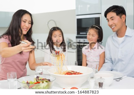 Happy woman serving spaghetti for the family in the kitchen at home
