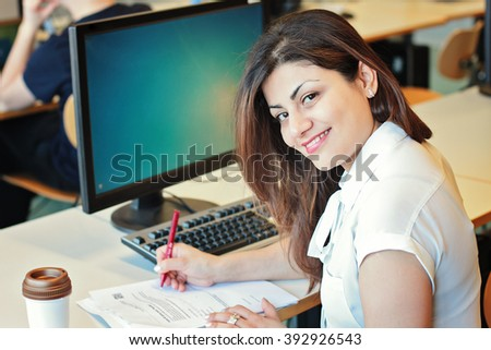Happy woman sitting at pc and write on paper