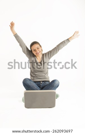 Happy woman sitting cross legged on floor with a laptop and arms raised up, on white background. Work from home. On-line study.