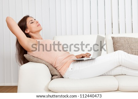 Happy Woman Sitting On The Sofa Using Laptop.