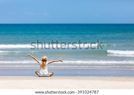 Happy woman traveler admiring her vacation on a perfect tropical beach