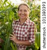 Happy woman with harvest of corn in  field - stock photo
