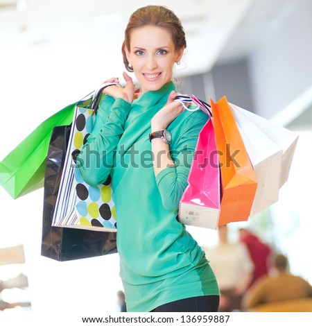 Happy woman with shopping bags in mall center. Sales.