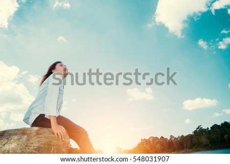 Happy woman with sit down on rock and lagoon at sunset