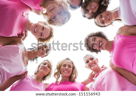 Happy women smiling in circle wearing pink for breast cancer on white background
