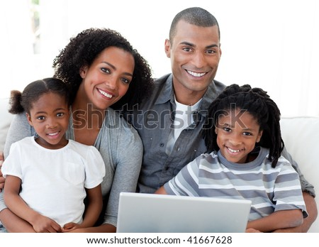 Happy young Afro-American family using a laptop in the living-room