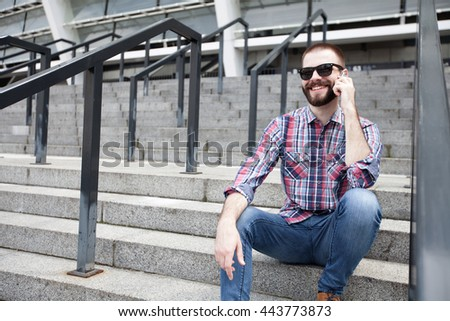Happy young bearded man talking on the mobile phone and smiling while sitting near
