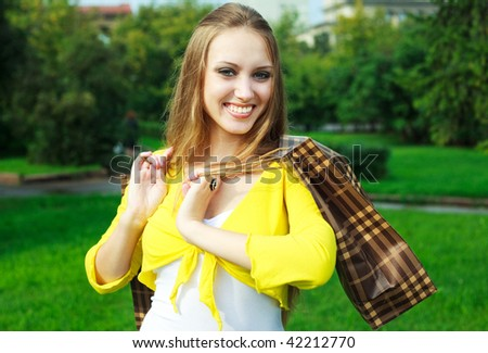happy young blond woman in the park with shopping bags