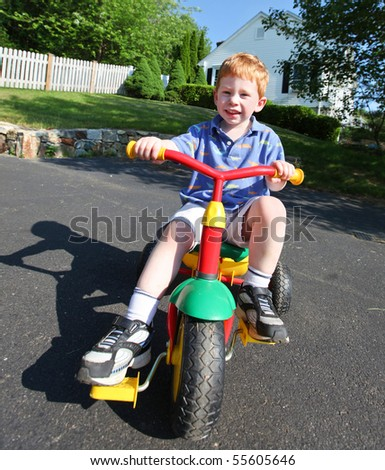 Happy young boy playing outside on a bike