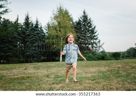 Happy young boy running on the grass in the afternoon sunset in the park