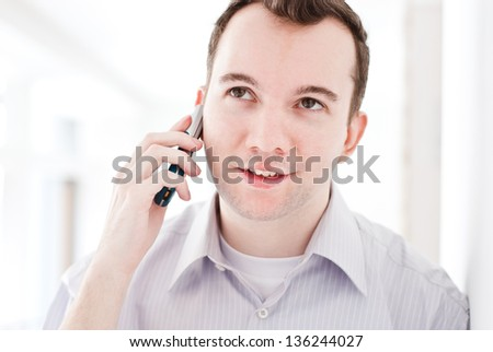 Happy young brown-haired businessman talking on mobile phone with the customer in the bright office building