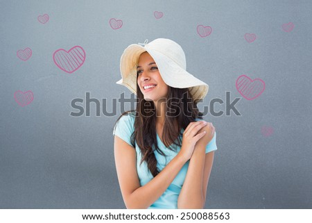 Happy young brunette wearing sunhat against grey