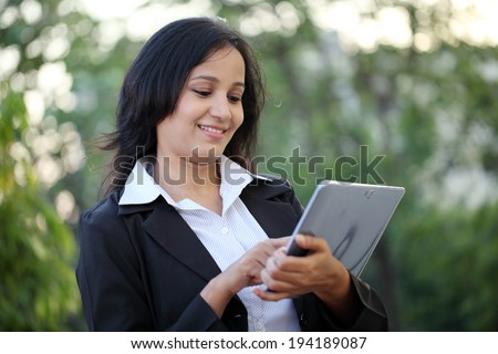 Happy young business woman with tablet computer at outdoors