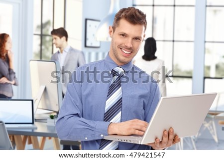 Happy young caucasian stock broker at business office with laptop computer in hand. Standing, smiling, looking at camera. Tie, no jacket.