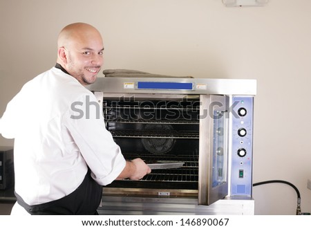 Happy young chef cooking steak in the oven