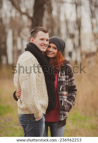 Happy young couple embracing and having fun together outdoors in autumn