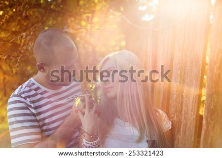 Happy young couple in love hugging and kissing outside next to the wooden fence
