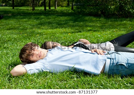 Happy young couple lying on the grass in summer park together and relaxing