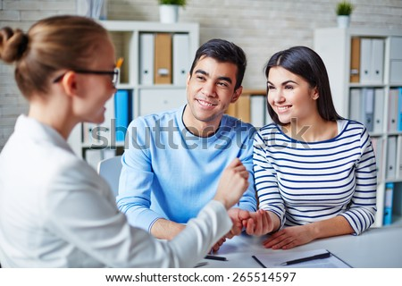 Happy young couple making deal with realtor