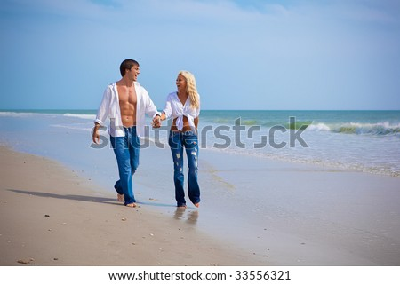 Happy young couple on vacation walking on a beach, both wearing jeans and white shirts.