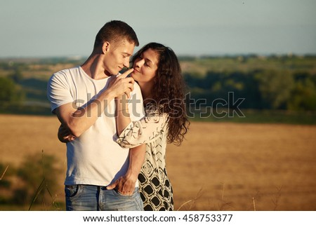 happy young couple posing high on country outdoor over yellow field, romantic people concept, summer season