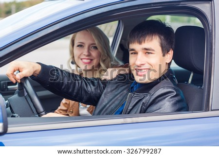 Happy young couple sitting in their car