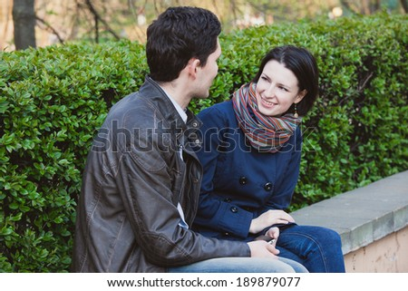 Happy young couple talking in the park